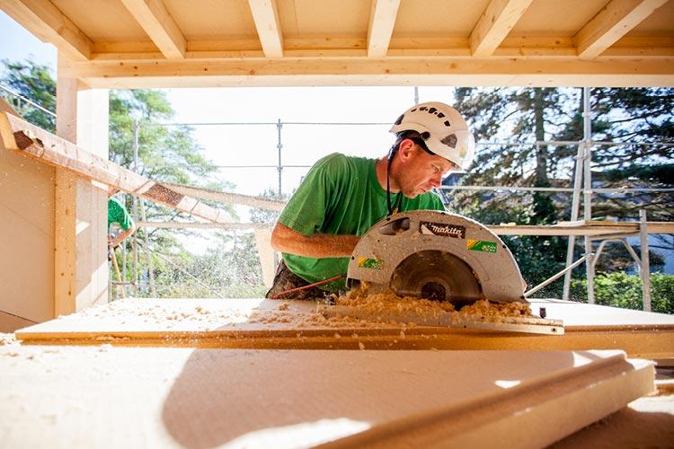 Holzbau Mitarbeiter arbeitet am Dachausbau eines Einfamilienhauses in Basel